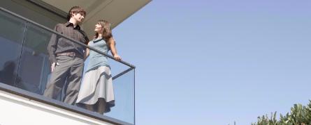 Mann und Frau stehen glücklich auf dem Balkon ihrer neu erworbenen Immobilie.