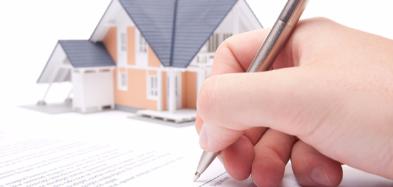 Eine Hand unterschreibt ein Papier, im Hintergrund ein Haus.