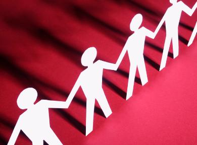 Menschenreihe aus Papier, roter Hintergrund.